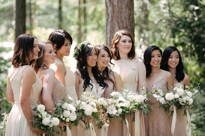 bridesmaids in neutral colored gowns holding green and white bouquets