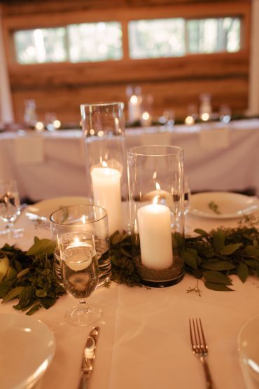 wedding centerpiece with candles and foliage runners