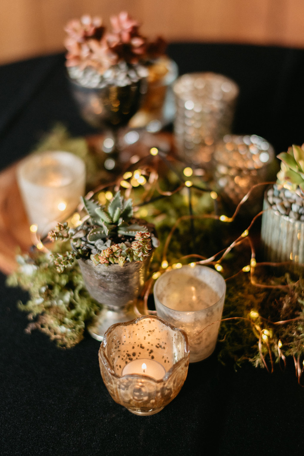 centerpiece with potted succulents mercury glass candles and fairy lights