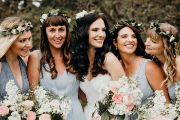 Bride and her bridesmaid wearing flower crowns with lush foliage and blush and white flowers for a Whidbey Island wedding at Comforts Winery