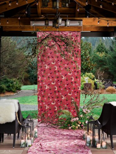 Wedding flower installation with branches and a velvet print backdrop