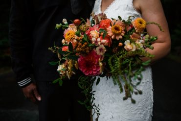 Lush boho bridal bouquet brimming with locally grown summer flowers for a destination wedding elopement on Whidbey Island | peach, coral and blush Zinnia, Dahlia, Celosia and more | Wedding Flowers by Tobey Nelson