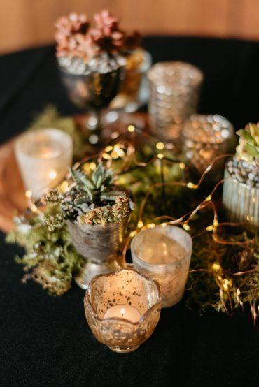 Mixed sedum centerpiece with fairy lights, moss, and wood slice