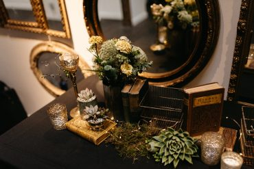Wedding tablescape close up with bridal bouquet, sedums, and vintage accessories