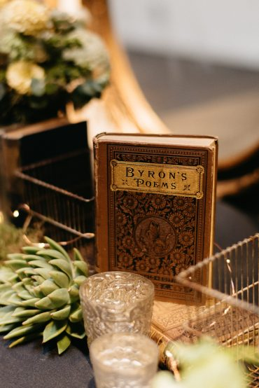 Candles, sedums and vintage books for a wedding welcome table
