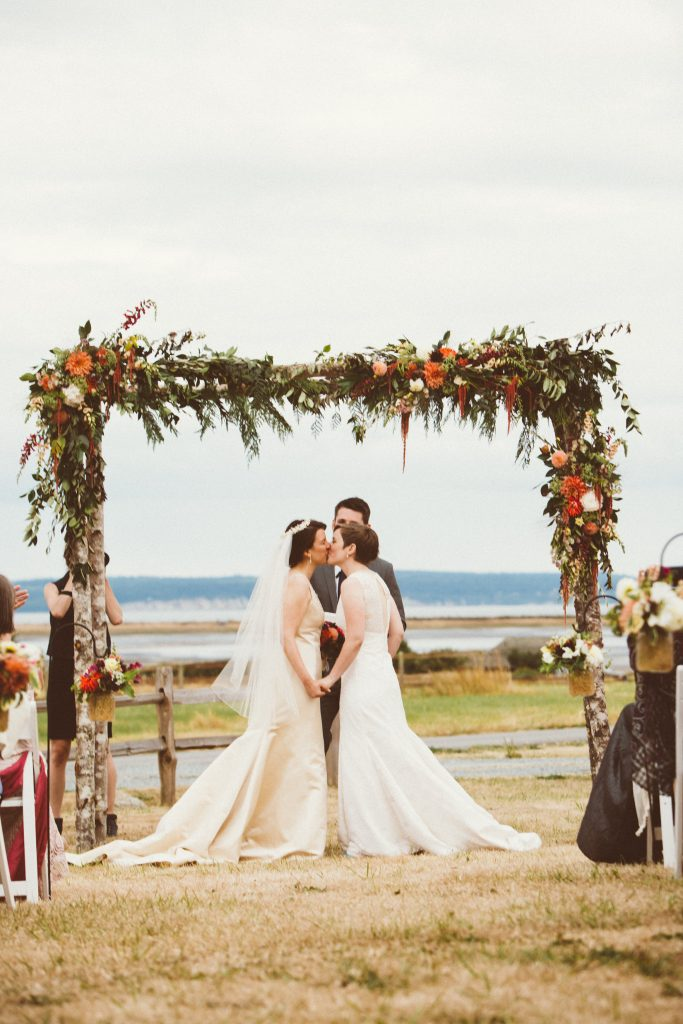 Wedding Arbors with locally grown flowers and greenery for Whidbey Island Gay Wedding by Tobey Nelson Events + Designs. Image by Sullivan & Sullivan Photography.