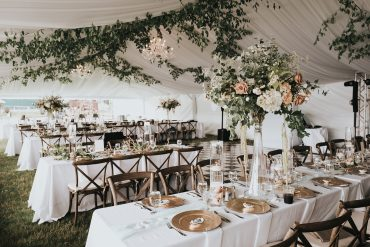 San Juan Island Wedding features a tent with elevated centerpieces and a greenery draped ceiling | Florals by Tobey Nelson Events | Venue Roche Harbor Resort on San Juan Island | photography by Sullivan & Sullivan