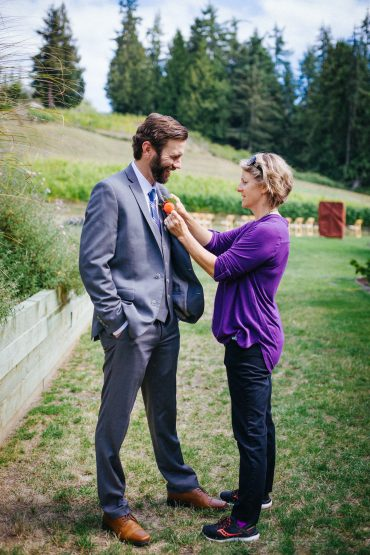 Whidbey Island Wedding planner Tobey Nelson pins a boutonniere on the groom