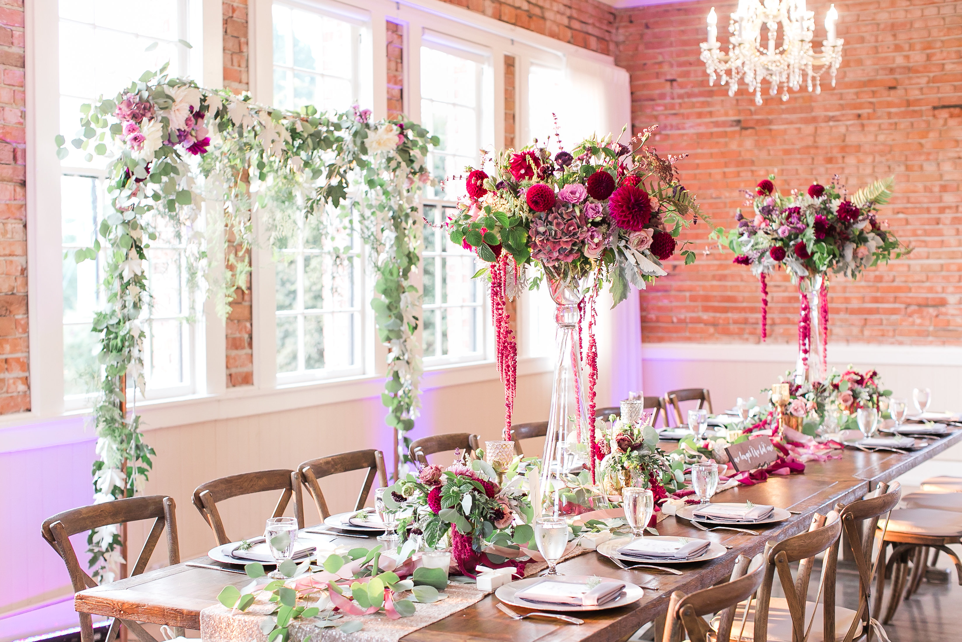 Head table at a wedding reception with elevated centerpieces and a greenery backdrop
