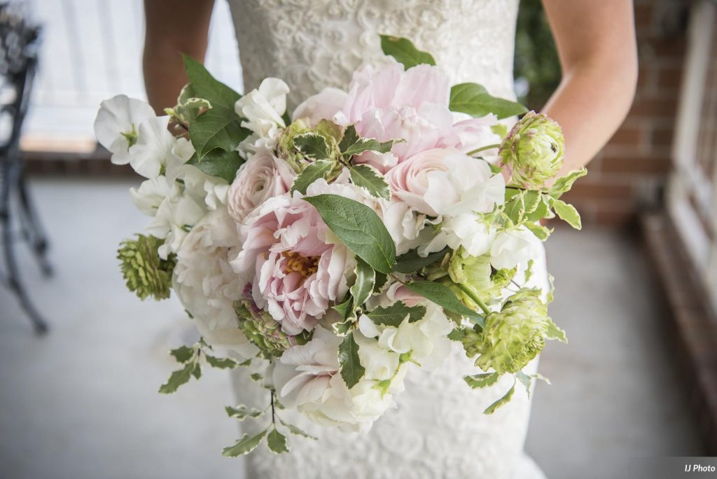 Spring bridal bouquet by Tobey Nelson Events features blush Peony, Ranunculus, Sweet Peas, and lush greenery