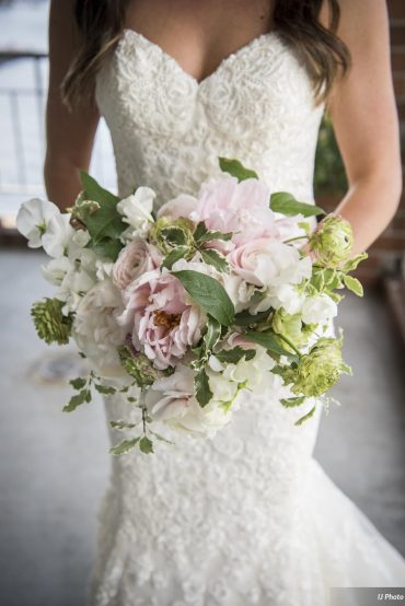 Lush and yummy spring bridal bouquet with blush Peonies, Ranunculus, Sweet Peas and greenery. Floral design by Tobey Nelson Events for a Woodmark Hotel wedding. Photo by IJ Photography