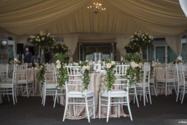 Tented wedding features chair decor, elevated centerpiece with Peonies and Roses