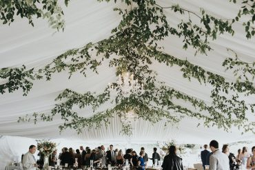 San Juan Island wedding flowers by Tobey Nelson | Tent ceiling greenery | image by Sullivan & Sullivan