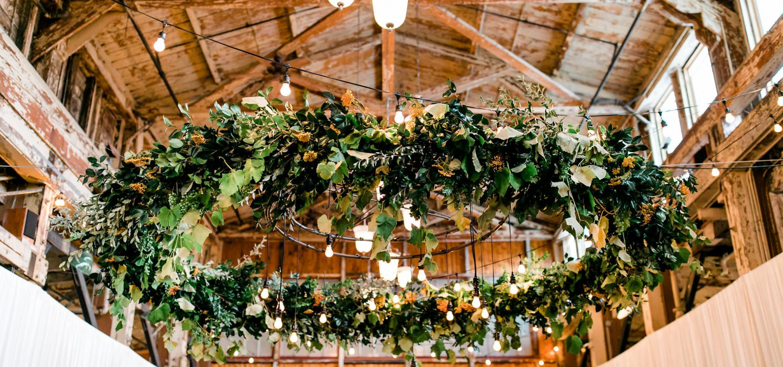 Sodo Park Seattle wedding greenery chandelier hanging installation by Tobey Nelson Events | image by Alante Photography