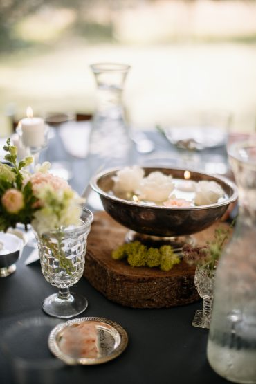 Collage centerpiece with vintage containers, wood rounds, moss and floating candles | Tobey Nelson Events | J Tobiason Photography