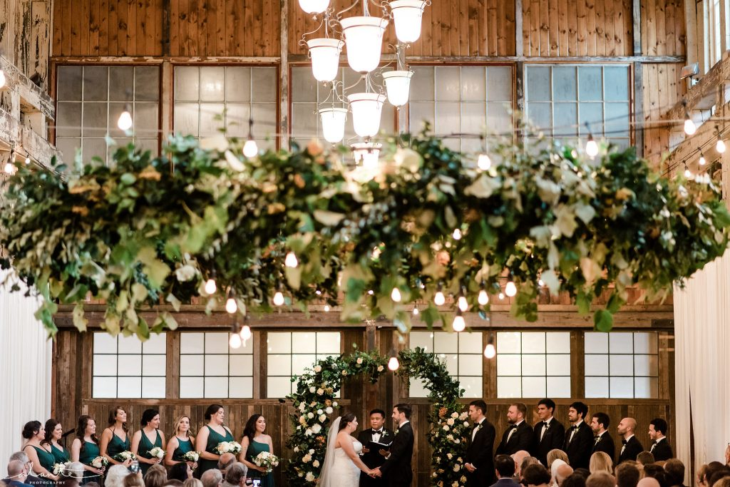 Seattle wedding at Sodo Park features foam-free floral arrangements including a greenery chandelier a greenery wedding arch | Floral and Event design by Tobey Nelson | image by Alante Photography