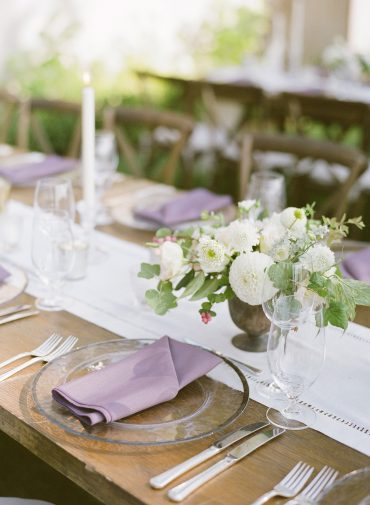 Table setting with glass chargers, lavender napkins, wood table, and hemstitch linen runner |backyard Lake Washington Lakeside wedding in Seattle | Flowers by Tobey Nelson Events | image by Katie Parra Photography | planning by The Invisible Hostess