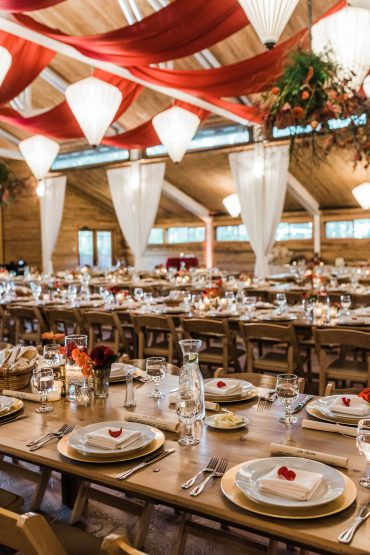 Event design with ceiling drape, foam-free floral installations, and wooden farm style tables for a non-profit fundraising gala at fireseed catering on Whidbey Island
