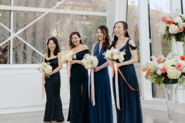 Bridesmaids in navy dresses with white and coral bouquets | Wedding Ceremony at Chihuly Glass Garden with flowers by Tobey Nelson Events photo by GH Kim Photography