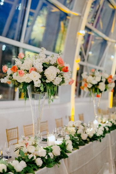 Head table decor | Foam-free elevated centerpieces with Hydrangea, Stock, Roses and Tulips | white and coral wedding flowers | Salal garland with pops of flowers | Wedding at Chihuly Glass Garden with flowers by Tobey Nelson Events photo by GH Kim Photography