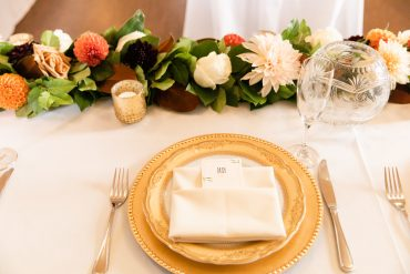 place setting with gold charger and flower garland