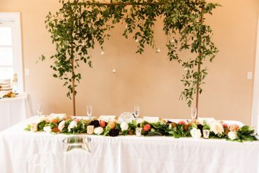 wedding head table with flower and greenery garland and a greenery backdrop