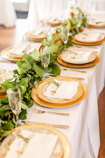 Wedding table with greenery garland and gold chargers