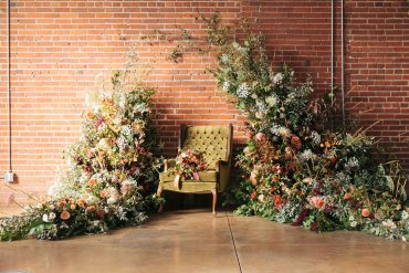 floral arch installation with green velvet chair