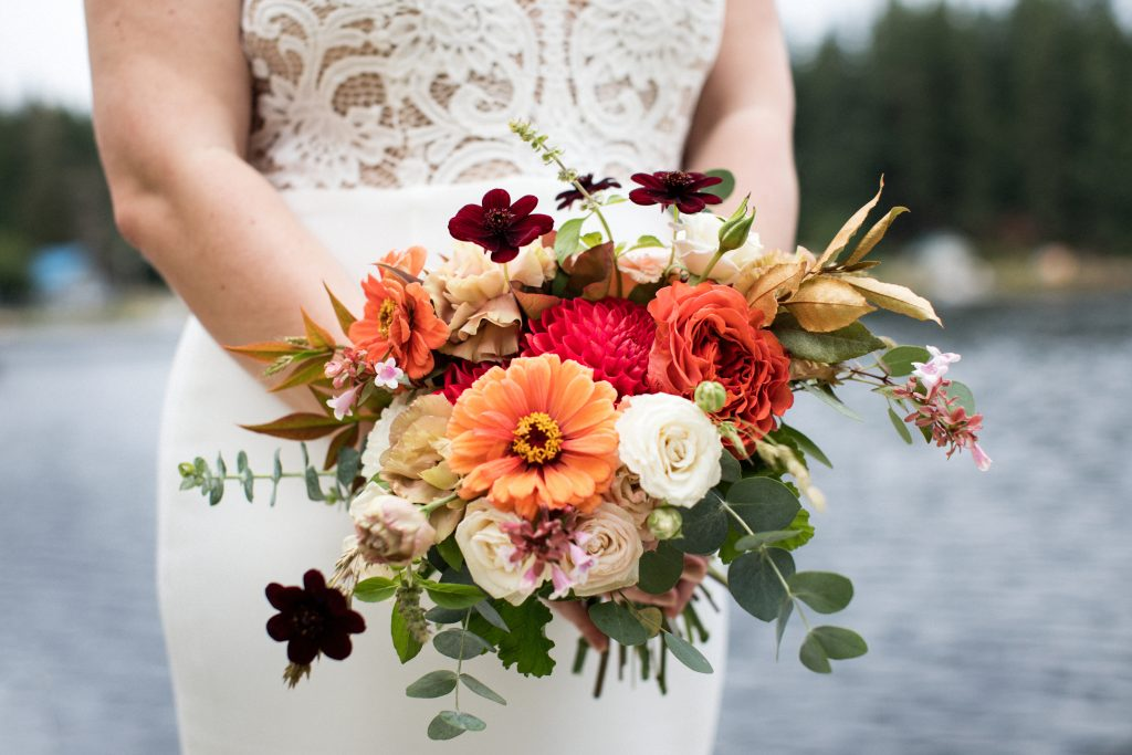 Coral, orange and white bridal bouquet with Zinnia, Dahlia, Rose and greenery | Dancing Fish Vineyards Whidbey Island wedding flowers by Tobey Nelson Events | image by Jenny Jimenez
