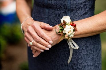 Wrist corsage with cream Rose and orange berries tied with a ribbon