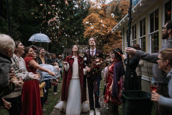 Wedding couple showered in flower petal confetti