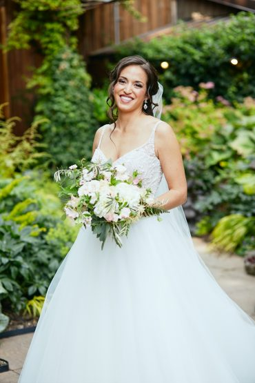 bride holding bouquet with white flowers and greenery