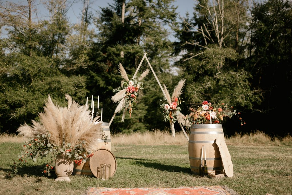 Backyard boho wedding ceremony with wine barrels, pampas grass, triangular arch and vintage rugs | Whidbey Island wedding flowers by Tobey Nelson Events | image by Carina Skrobecki