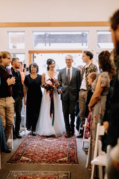 bride walking down aisle with parents, bridal bouquet and rugs on the ceremony aisle