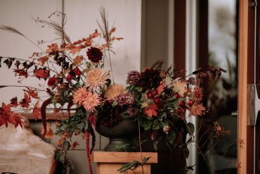 large cernterpiece with burgundy and peach Dahlias and fall foliage