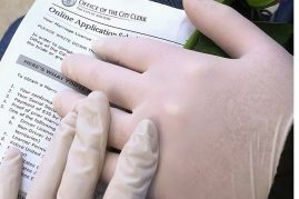 gloved hands with wedding ring and marriage license